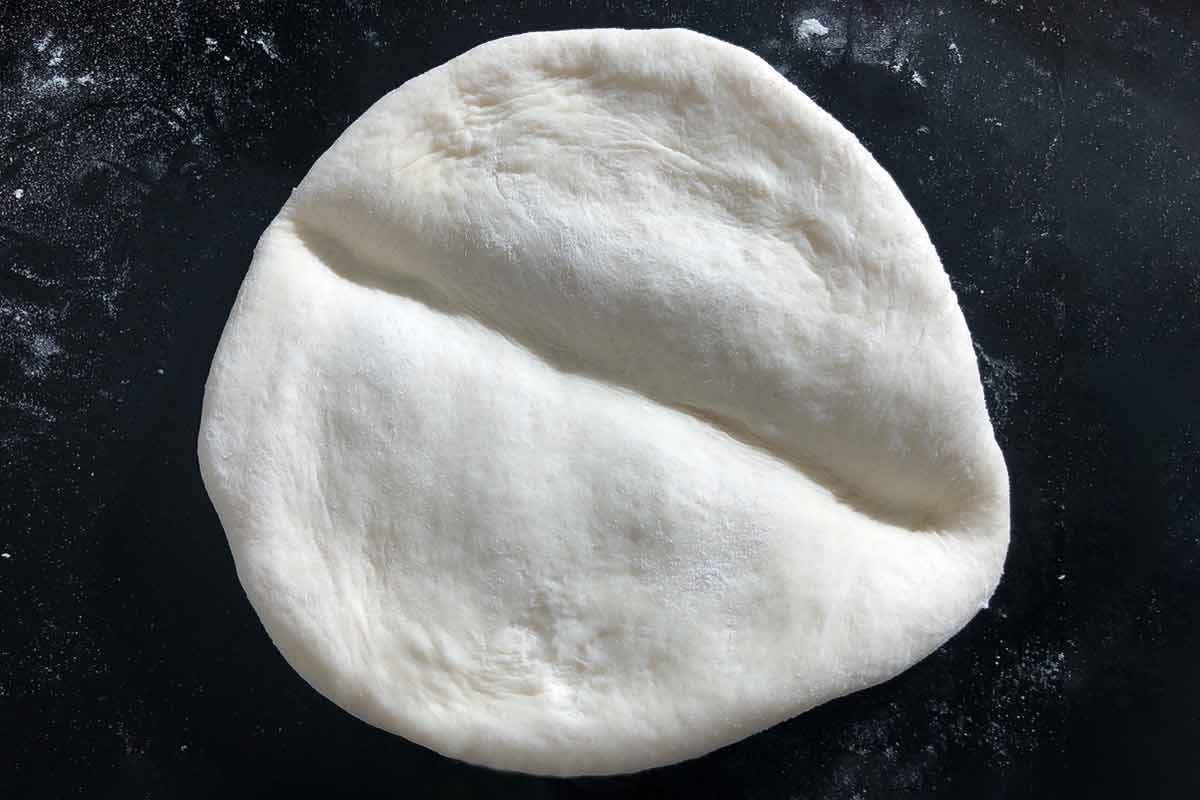 A round of papo-secos dough with a crease in the center.