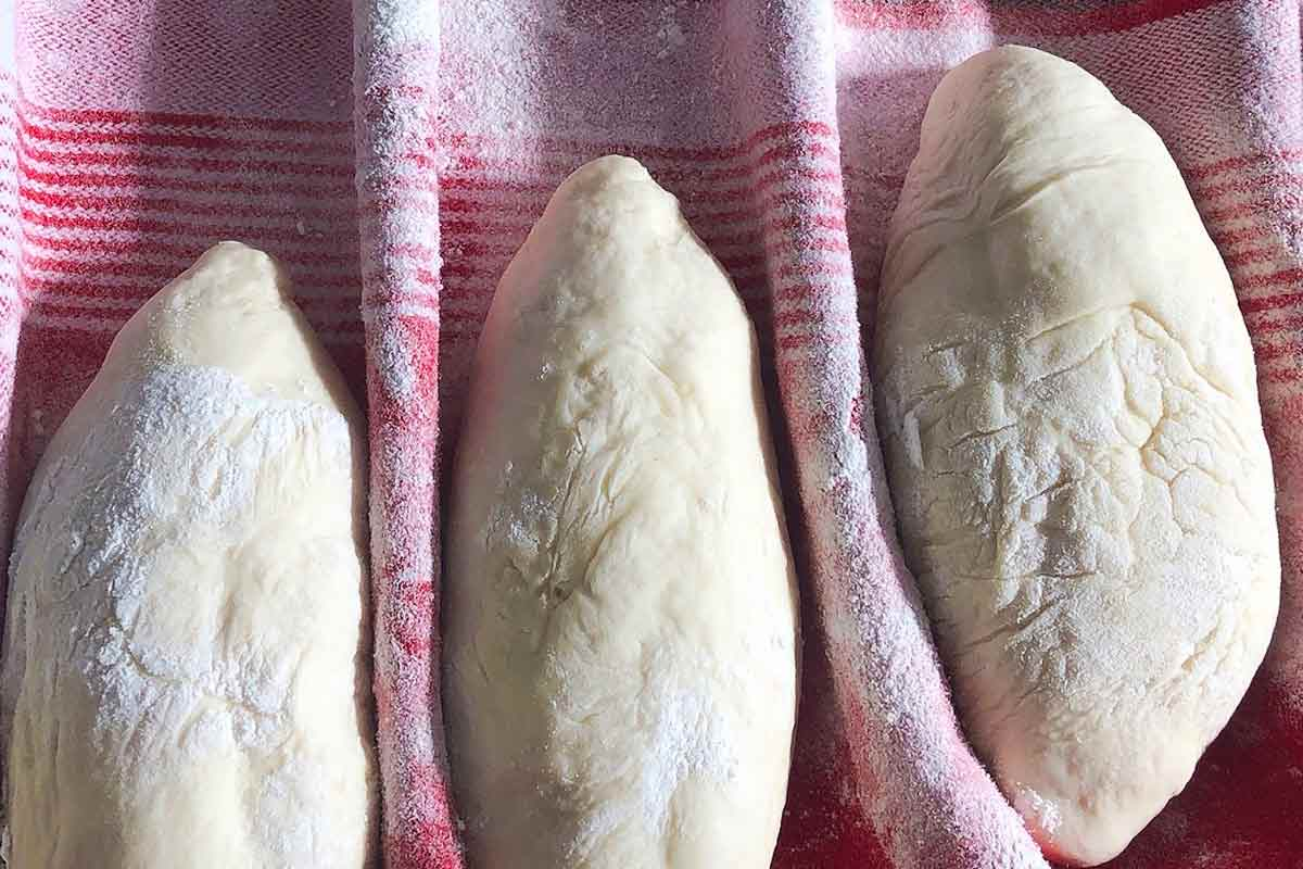 Three unbaked papo-secos rising on a ridged towel.