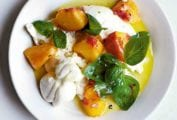 A white bowl filled with peach, burrata, and basil salad.