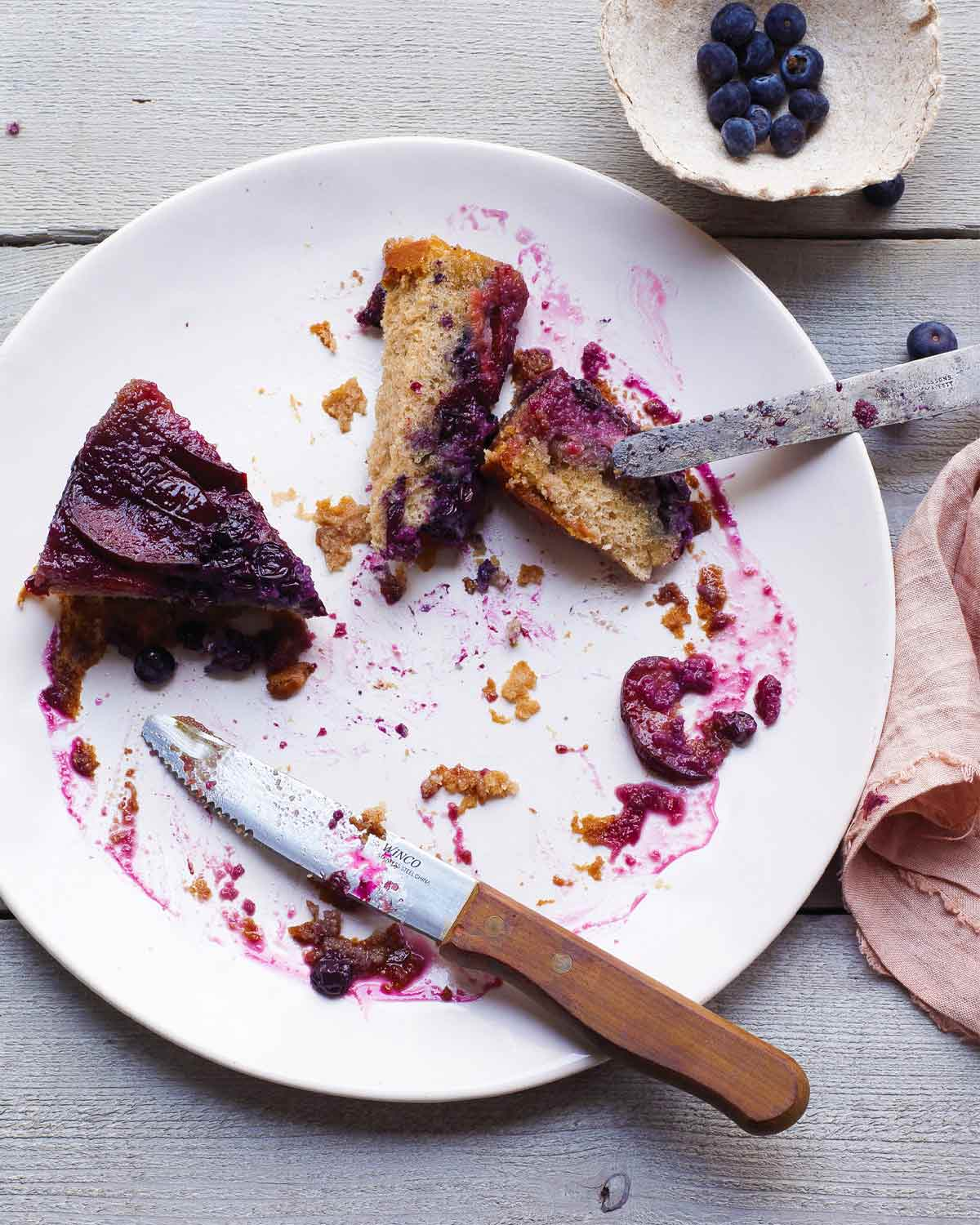 A couple slices of plum-blueberry upside-down cake on a white plate with a knife resting on the edge of the plate.