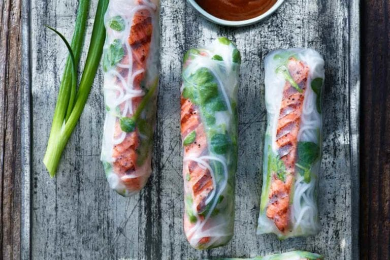 Four salmon summer rolls on a metal sheet with a piece of scallion and a bowl of dipping sauce.