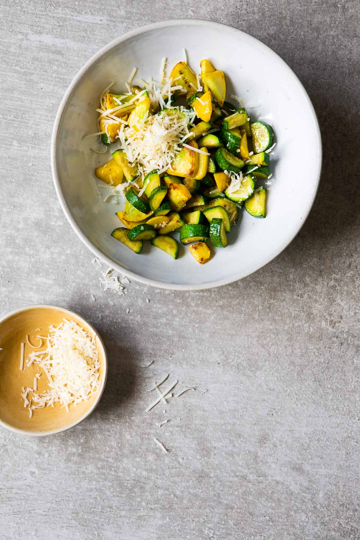 A white bowl filled with sautéed summer squash with a sprinkle of Parmesan on top and a small bowl of Parmesan on the side.