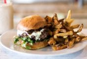 A skillet cheeseburger with arugula and a pile of fries on a white plate.