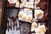 A tray of s'mores brownies with a spatula resting inside and several brownies missing.