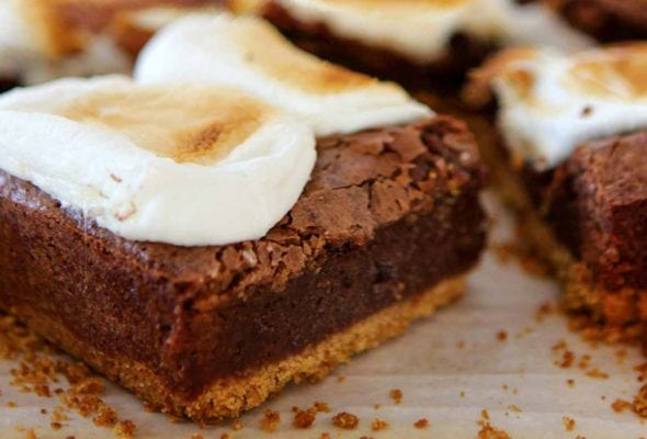 Several bars of cut s'mores brownies made with graham crust, fudgy layer and topped with marshmallow on a piece of parchment.