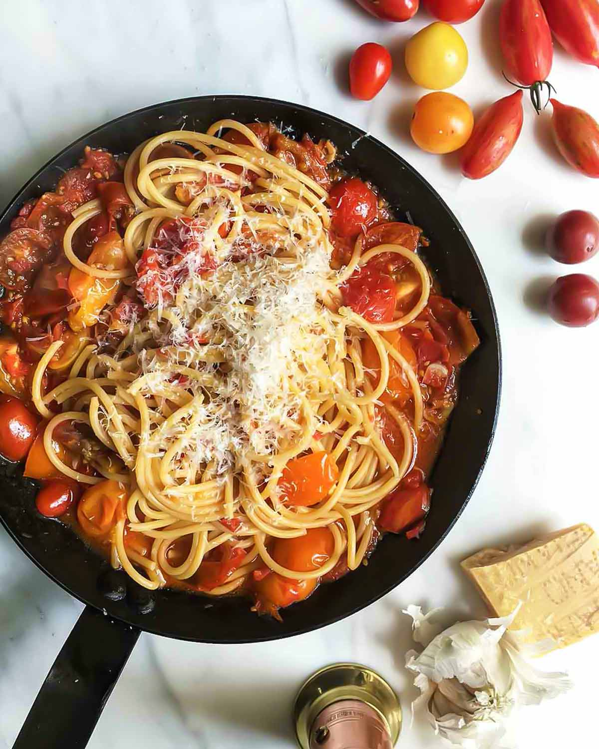 A black skillet filled with summer tomato pasta, sprinkled with fresh Parmesan cheese.