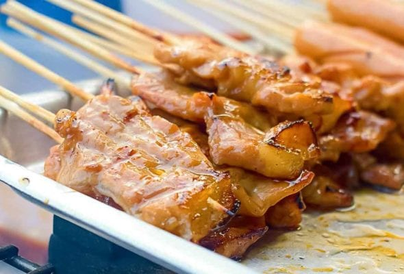 Skewers of thinly sliced Thai-style grilled pork skewers on a metal tray in a street food vendor's cart
