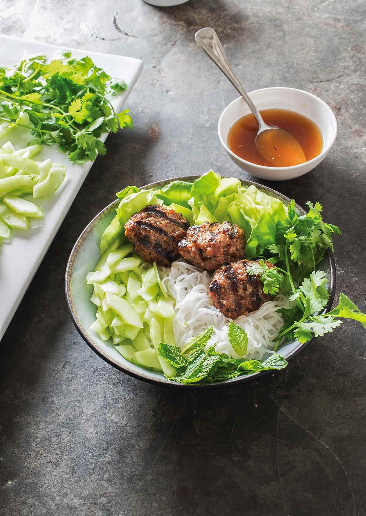 A dish filled with Vietnamese grilled pork patties with rice noodles and an crunchy vegetables.