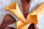 Vanilla and chocolate waffle cones on a white marble surface.
