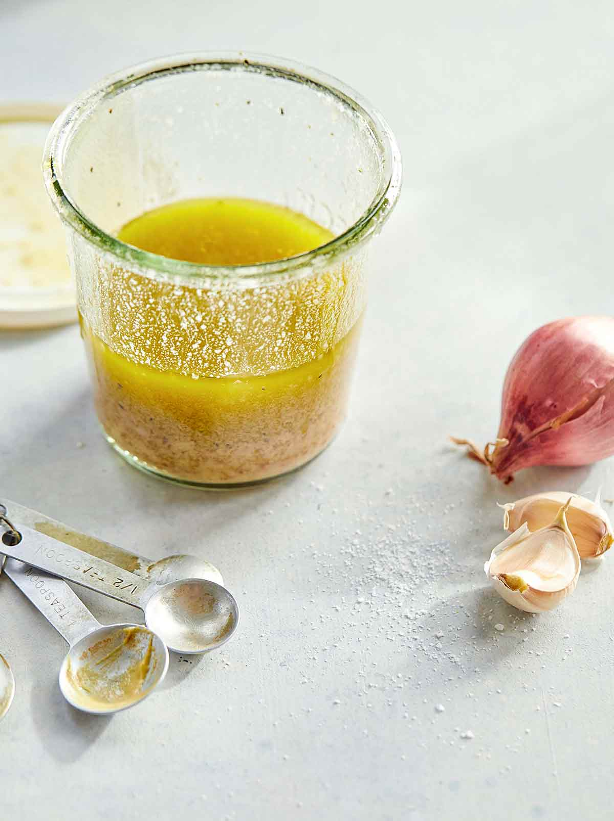 A glass jar half-filled with basic vinaigrette with measuring spoons, a shallot, and two garlic cloves on the side.