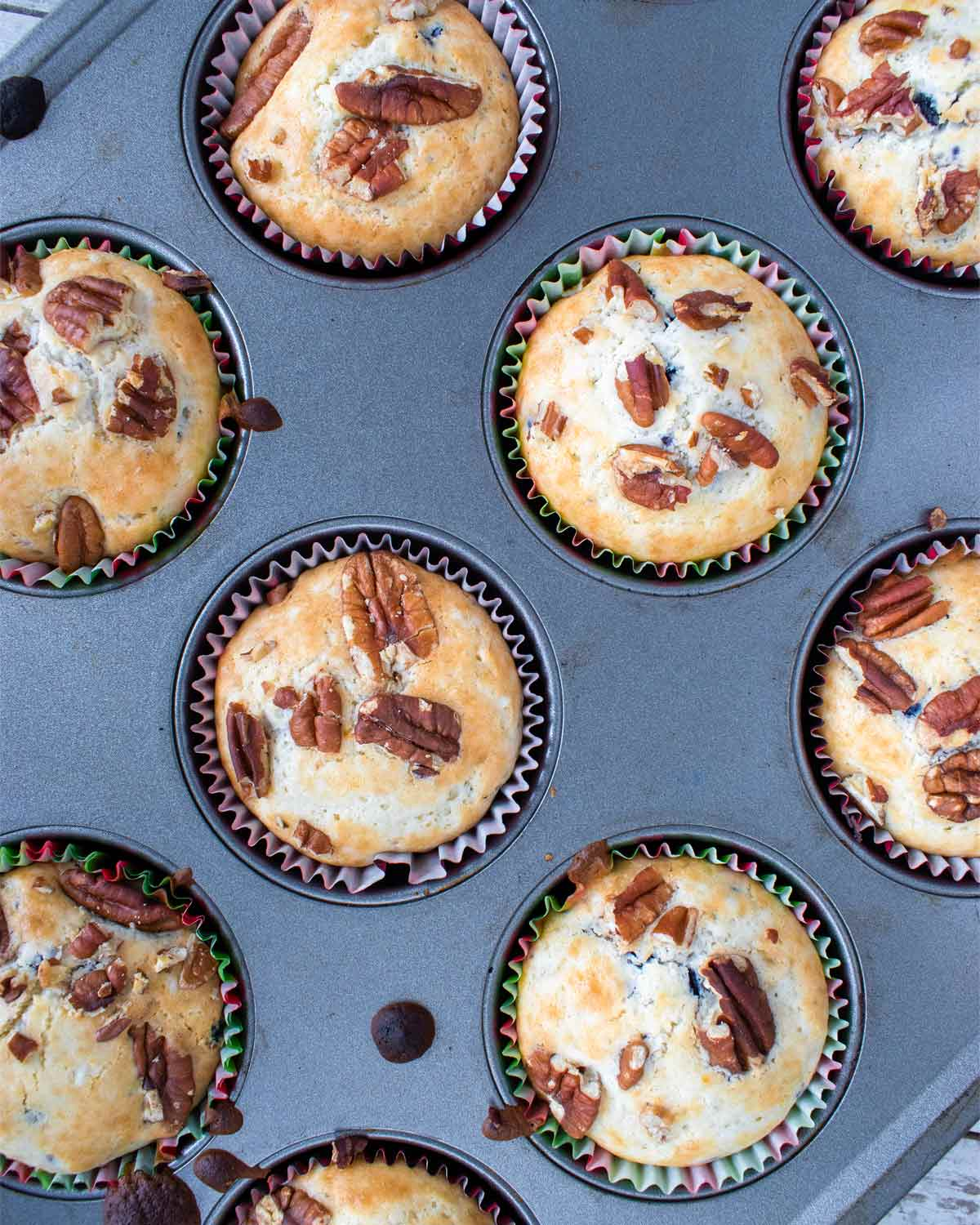 Baked blueberry pecan muffins in a muffin tin.