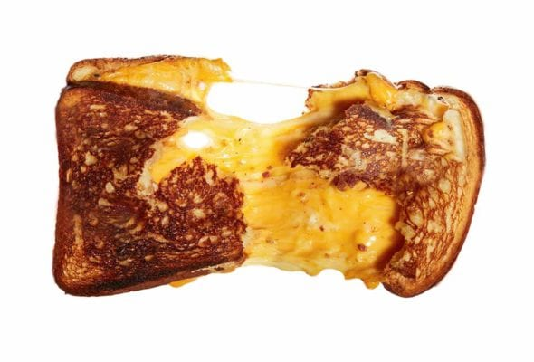 A challah grilled cheese sandwich torn in half, still connected by melted cheese.