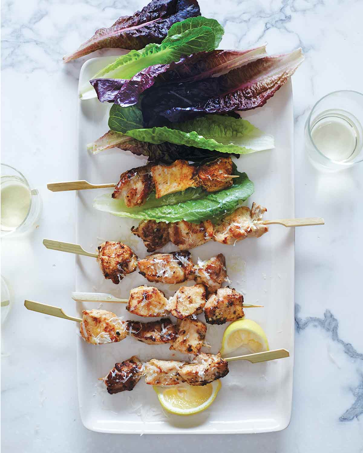 Six chicken caesar salad skewers on a white plate with leaves of red and green romaine and two lemon wedges.