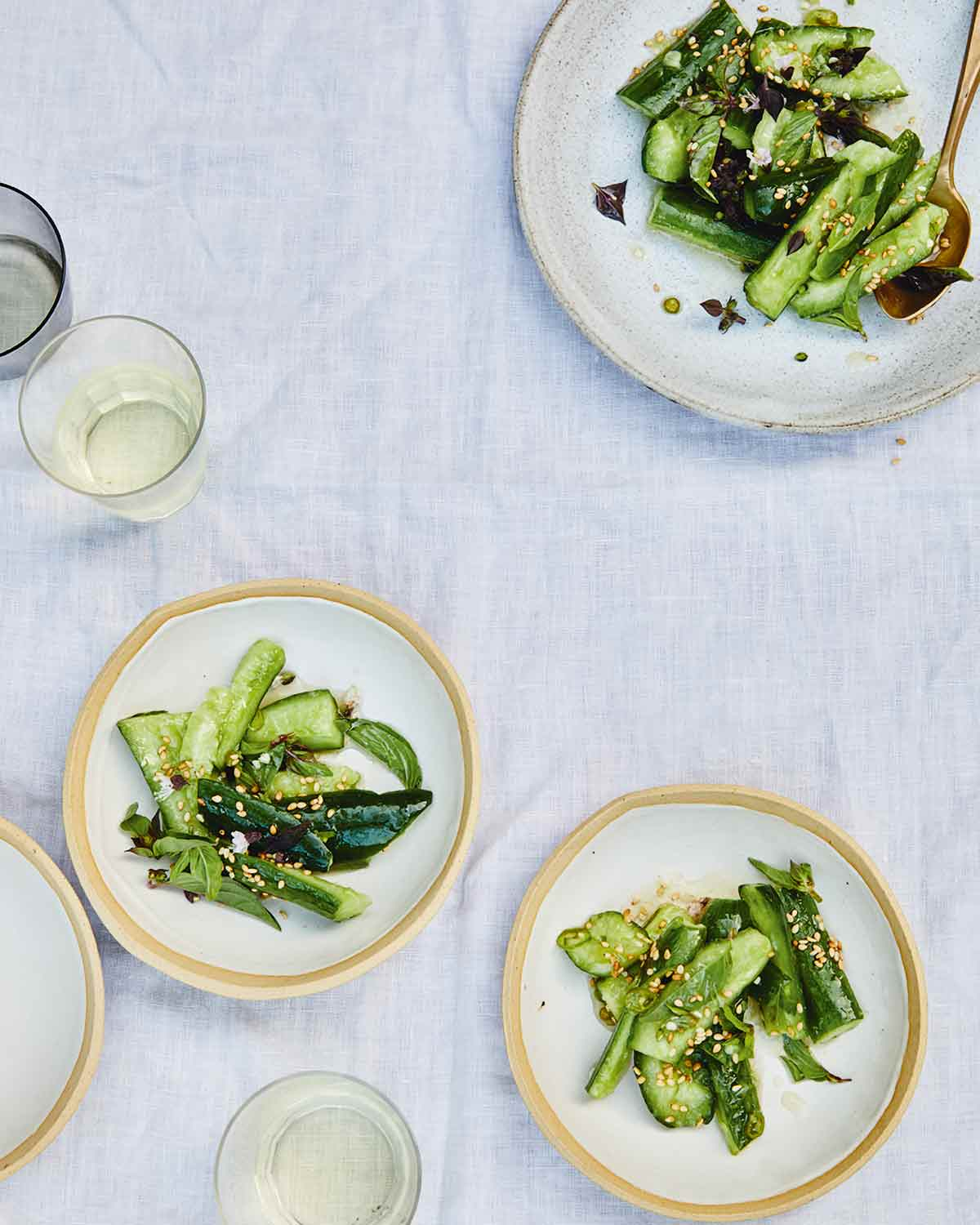 A serving plate and several individual plates topped with Chinese smashed cucumber salad.