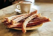 A plate of churros with a cup of hot chocolate in the background