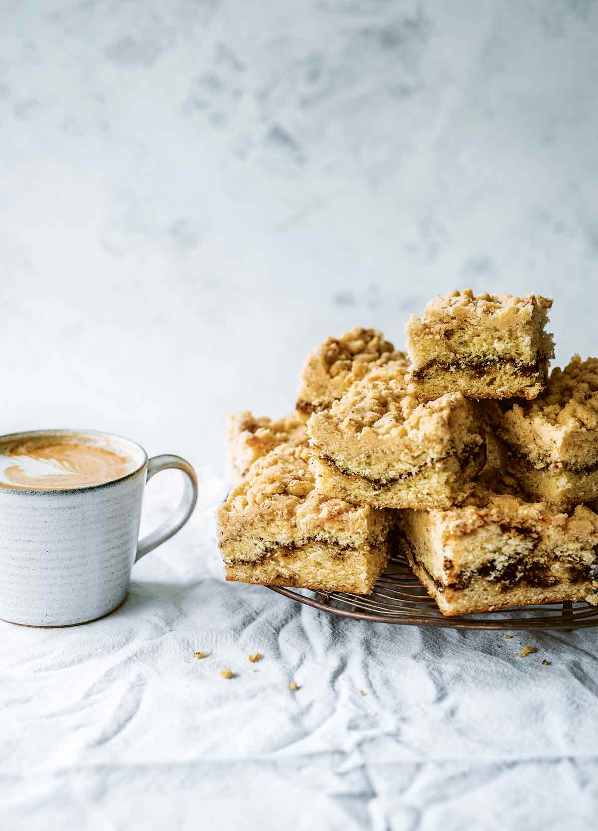 Several pieces of coffee coffee cake stacked on a wire rack, with a cup of coffee next to them.