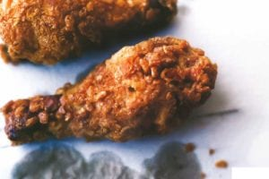 Three pieces of crispy fried chicken on grease-stained paper.