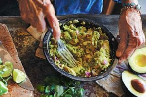 A person mashing avocado into a bowl of easy guacamole on a table with salt, avocado, cilantro, lime, and chiles.