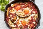 A cast-iron skillet filled with eggplant shakshuka made with poached eggs in a tomato and eggplant sauce, with feta scattered over the top.
