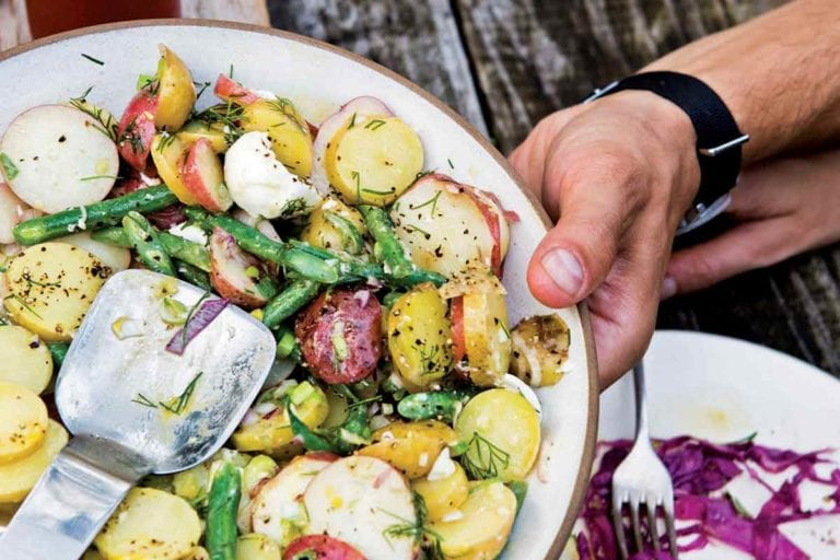 A person holding a platter of French potato salad above a wooden table.