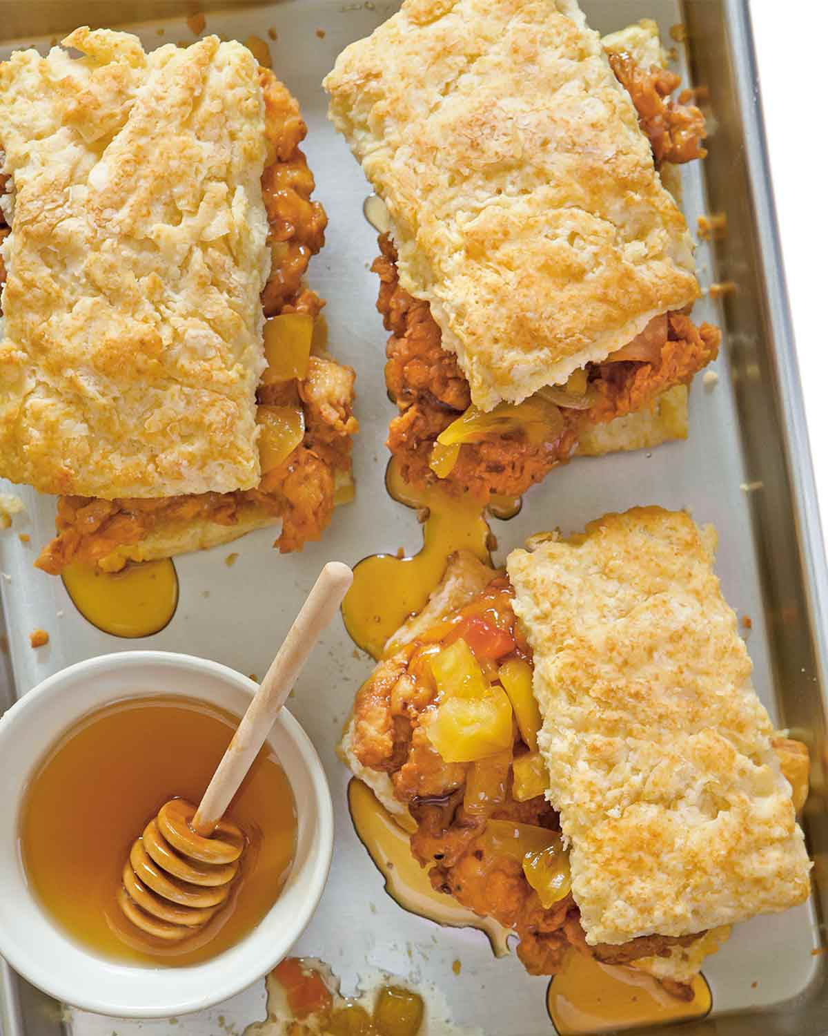 Three fried chicken and biscuits sandwiches on a baking sheet with a bowl of honey beside and drizzled around the sandwiches.
