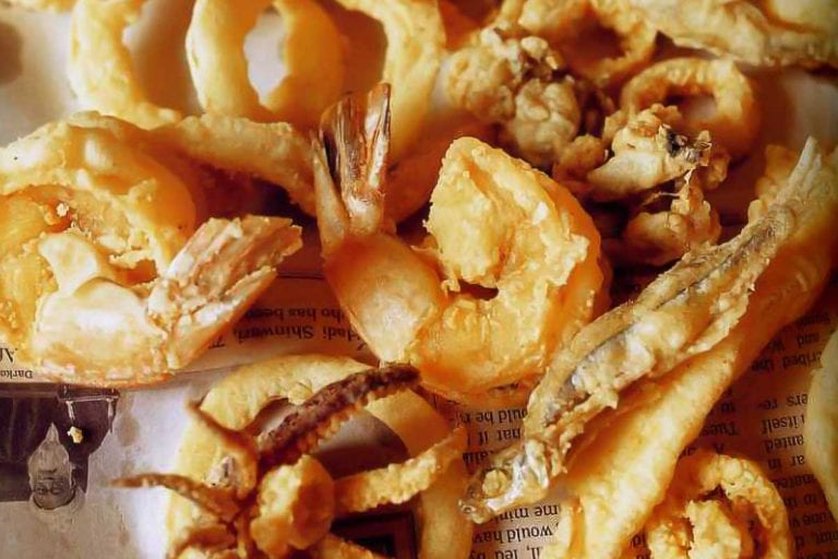 A pile of lightly fried shelfish - fritto misto amalfitano - on a piece of newspaper.
