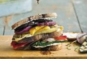 A grilled vegetable and goat cheese sandwich, made with grilled onion, eggplant, and squash on a cutting board being drizzled with balsamic vinaigrette.