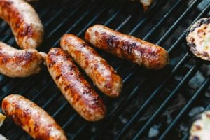 Grilled sausages and zucchini slices on a grill as part of an answer to 'how long does grilled food last?'.
