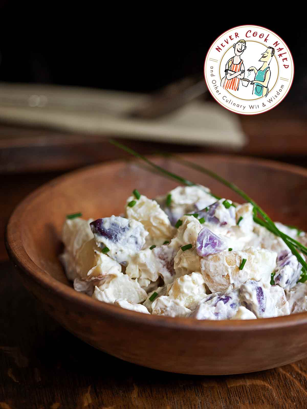 A wooden bowl filled with mayo-based potato salad as an illustration of how to store salad made with mayo.
