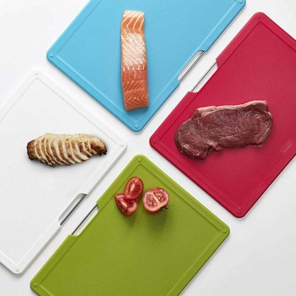 Different meats on different colors of the Joseph Joseph Folio Cutting Board Set.