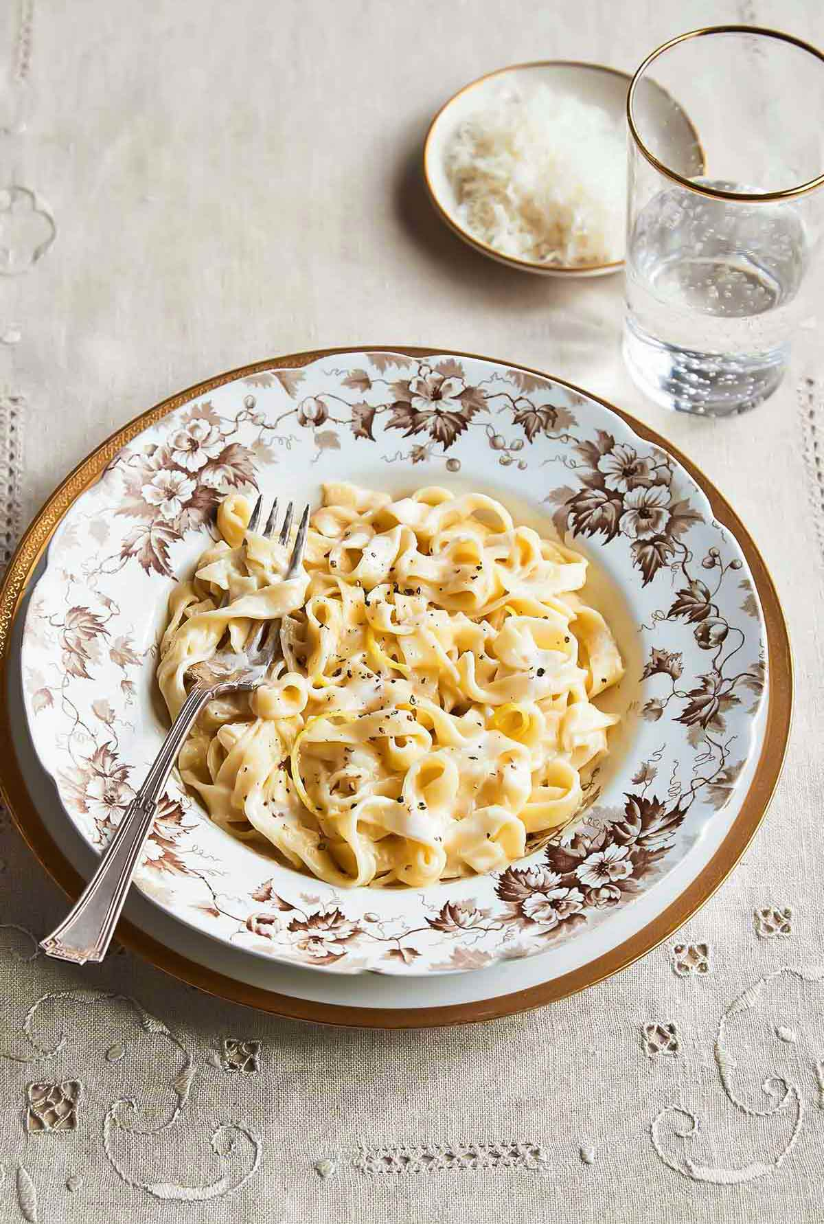 A patterned bowl filled with lemony fettuccine alfredo on a white and gold plate with a glass of water and dish of Parmesan on the side.