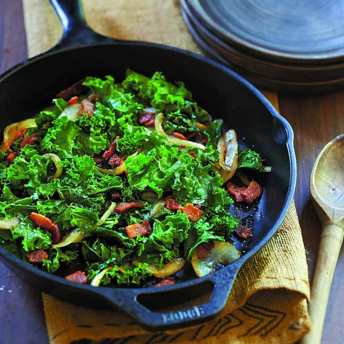 Lodge Pre-Seasoned Cast Iron Skillet With Assist Handle with greens in it.