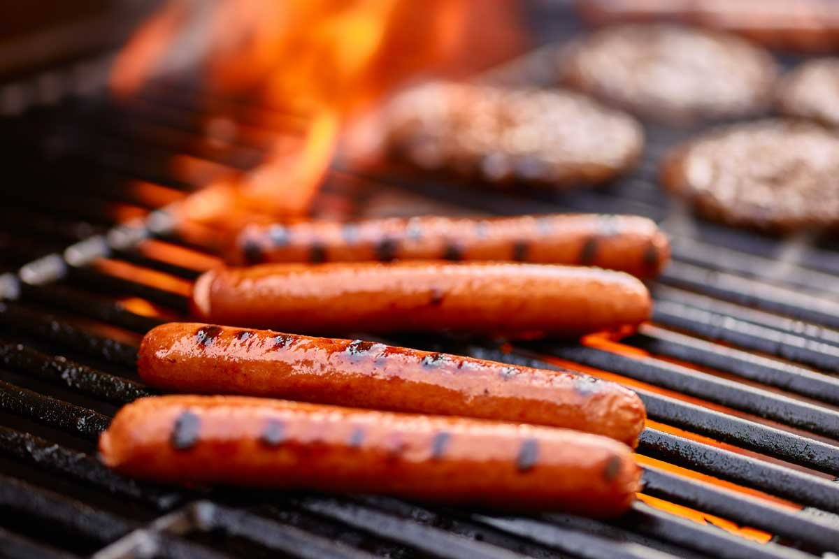 Hot dogs cooking on a grill to help explain Meathead's science of grilling.