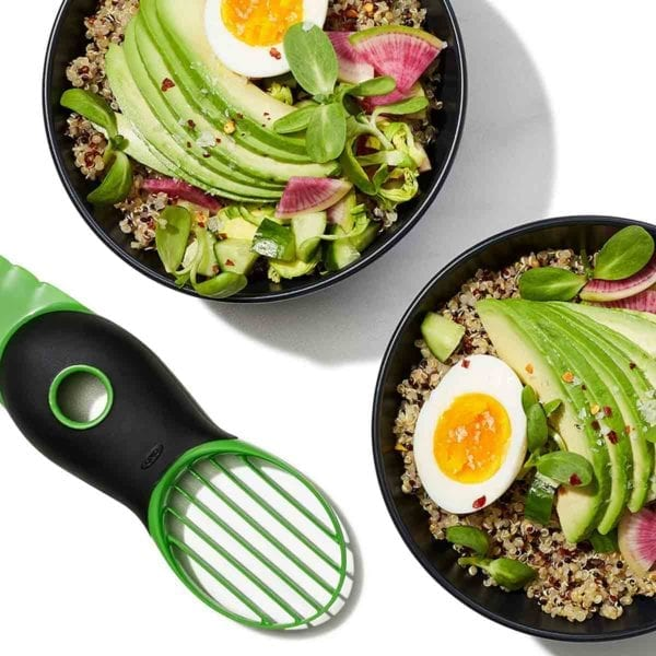 An OXO Good Grips avocado slicer next to two grain bowls topped with sliced avocado, soft boiled egg halves, and watermelon radish.