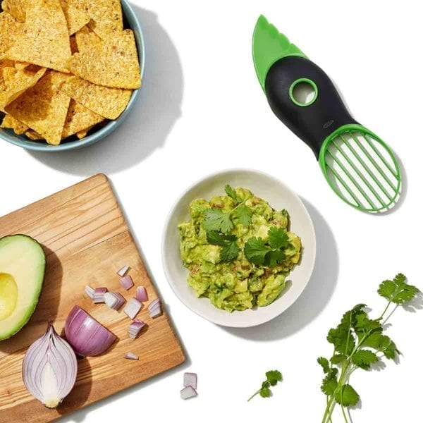 An OXO Good Grips avocado slicer lying next to a bowl of guacamole, a sprig of cilantro, a bowl of tortilla chips, and a wooden board with red onion and avocado on it.