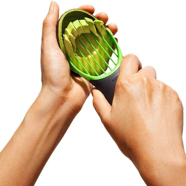 A person slicing an avocado using an OXO Good Grips avocado slicer.