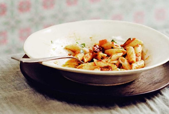 White bowl with ziti and a pasta puttanesca sauce