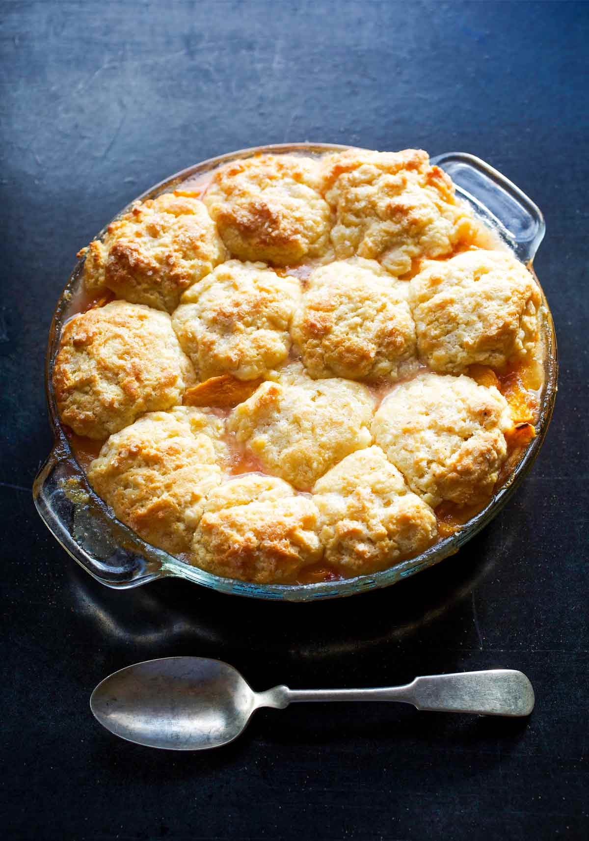 A round glass baking dish filled with peach nectarine cobbler and a spoon on the side.