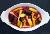 A white oval serving dish filled with pickled carrots.