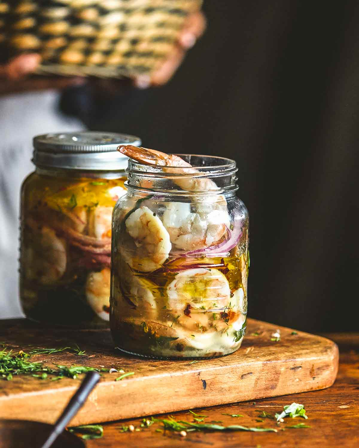 Two jars of pickled shrimp on a wooden cutting board.