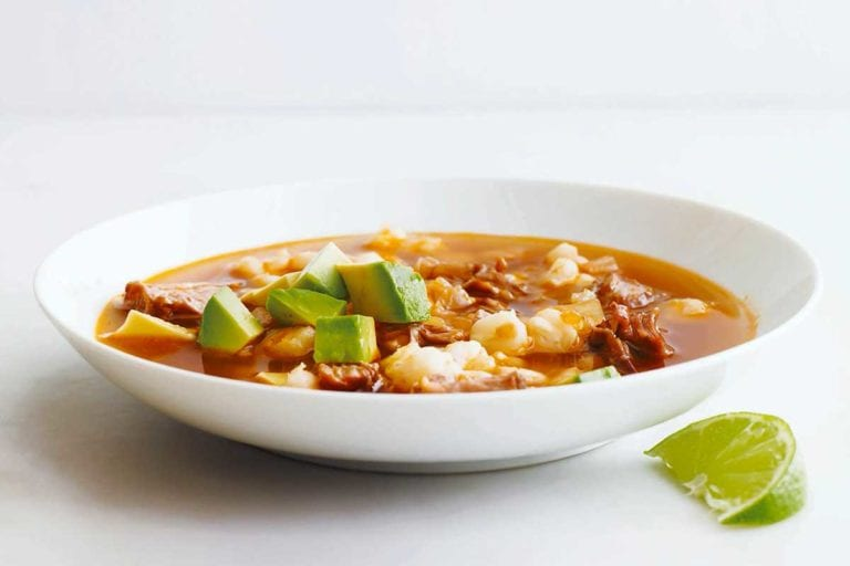 A white bowl filled with quick posole with pork topped with avocado with a lime wedge on the side.