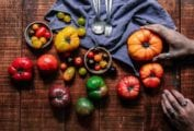 A wooden table filled with assorted tomatoes, a cloth napkin, spoons, and forks, and a person gently squeezing a tomato to check if it is perfectly ripe.
