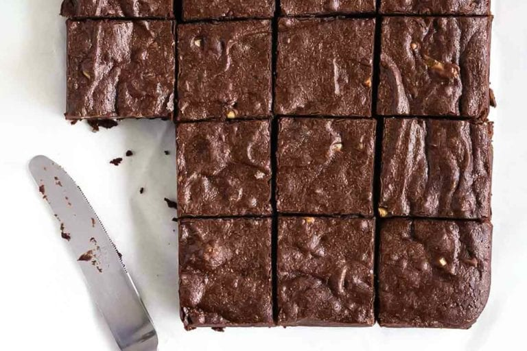 A batch of Rose Levy Beranbaum's fudge brownies cut into 16 squares, with two missing and a knife resting beside.