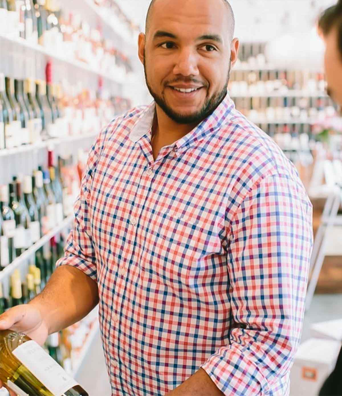 TJ Douglas showing a bottle of wine to a customer.