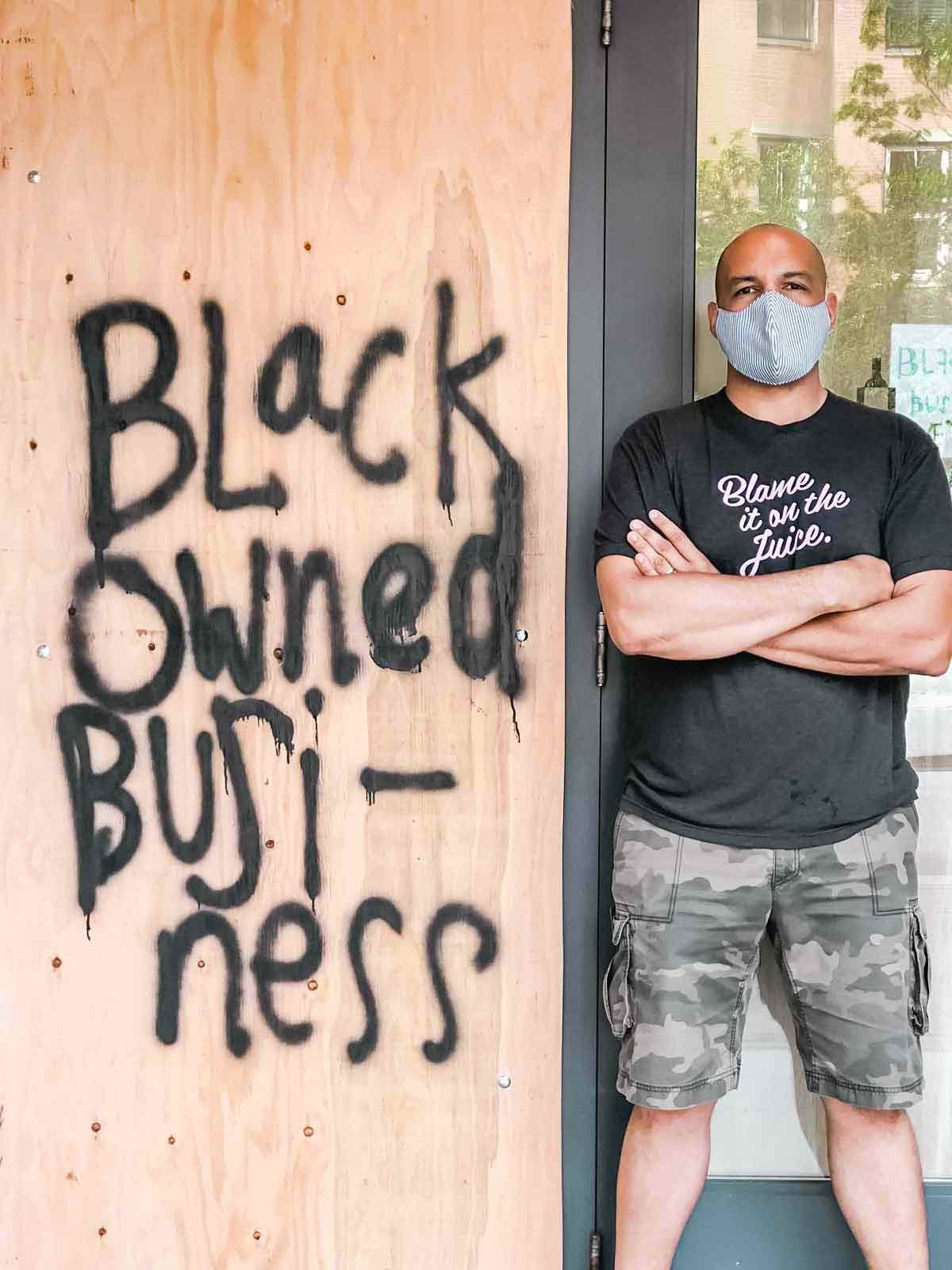 TJ Douglas standing beside a piece of plywood spray-painted with 'Black Owned Business'.