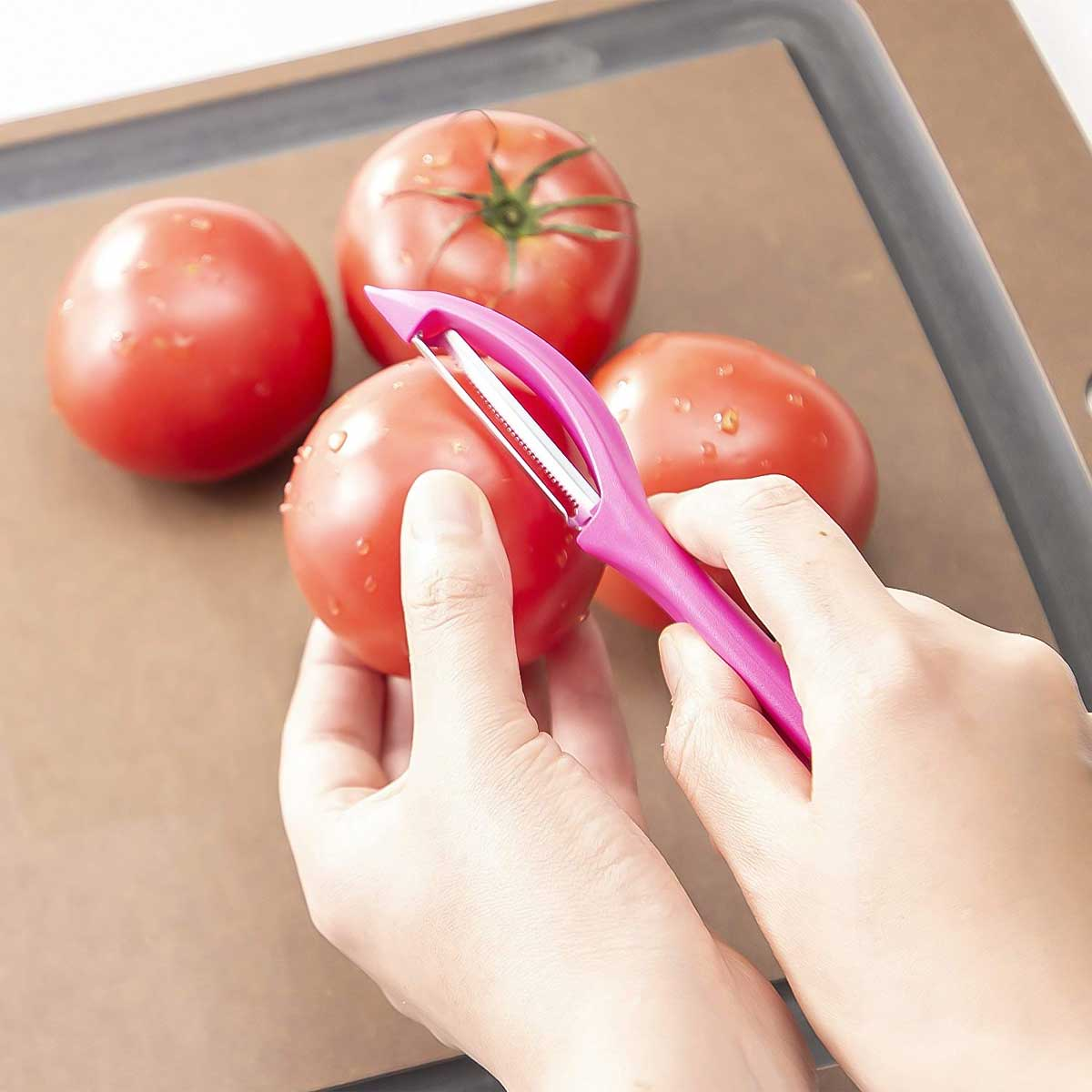 A person peeling tomatoes with a Victorinox serrated vegetable peeler.