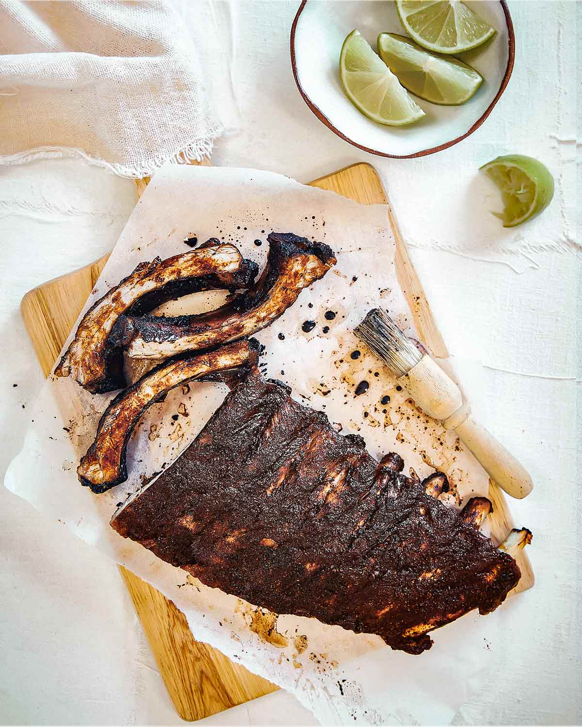 A rack of Vietnamese pork ribs on a sheet of parchment on a cutting board with a basting brush and a bowl of lime wedges nearby.