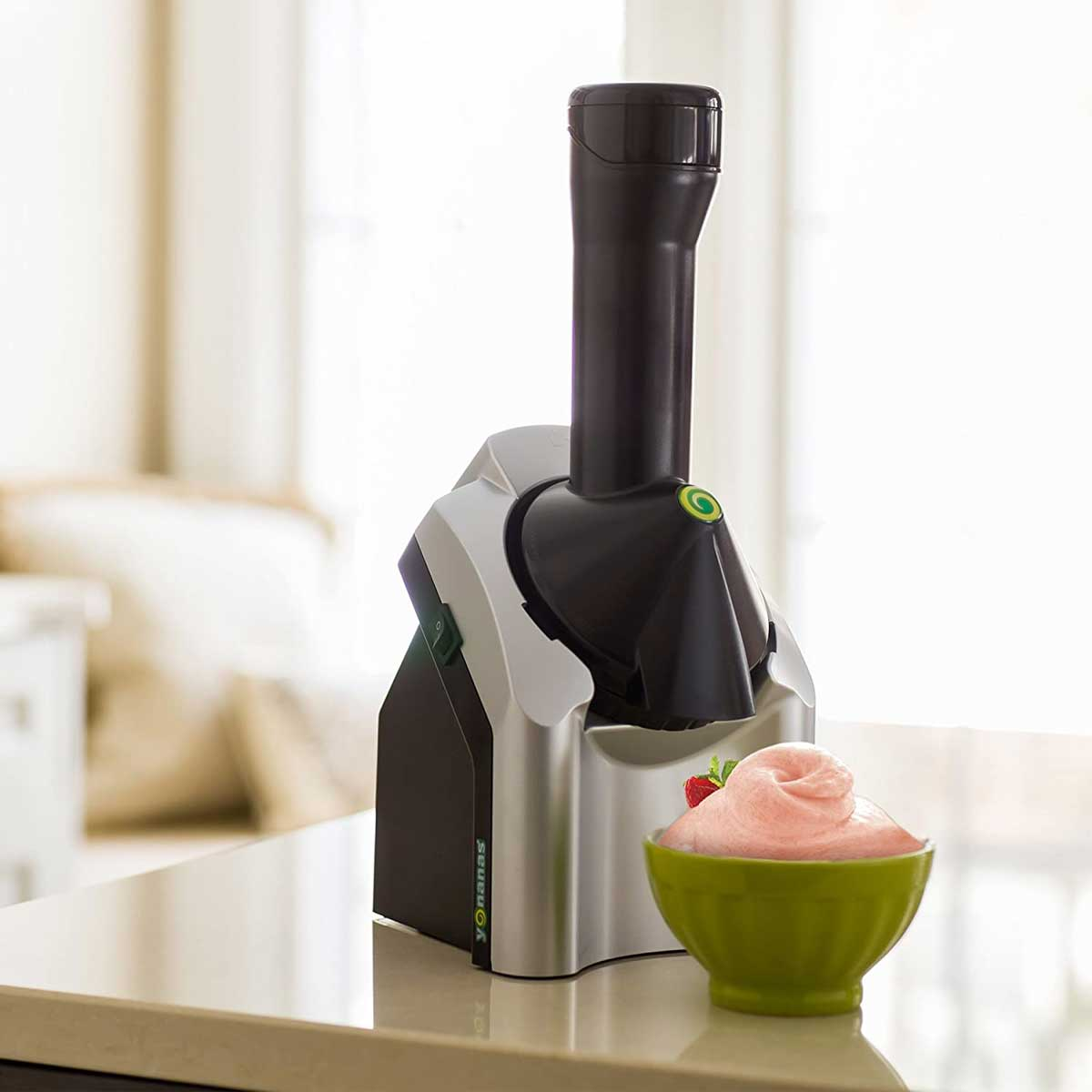 A Yonanas fruit soft serve maker with a bowl of homemade soft serve in a green bowl.
