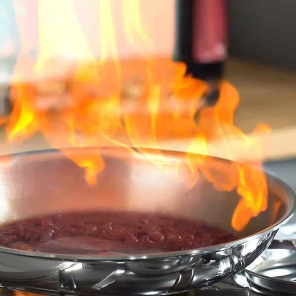 All-Clad D3 Stainless Cookware Set with a flame inside