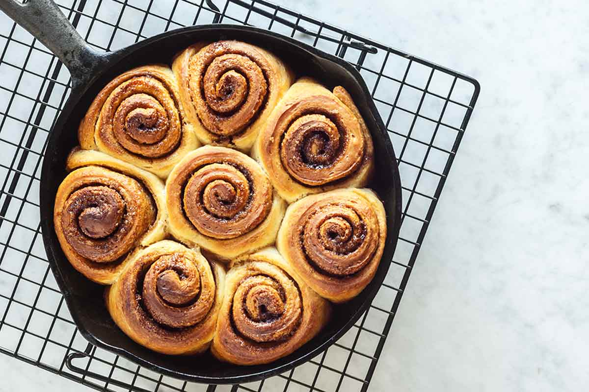 A cast-iron skillet filled with unglazed biscuit cinnamon rolls on a wire rack.